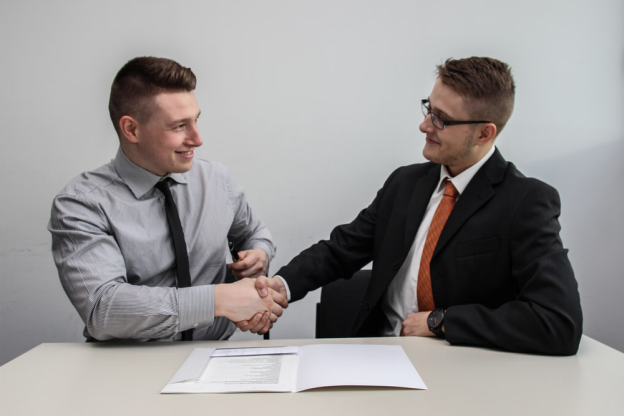 Candidate and hiring manager shaking hands after a successful interview.